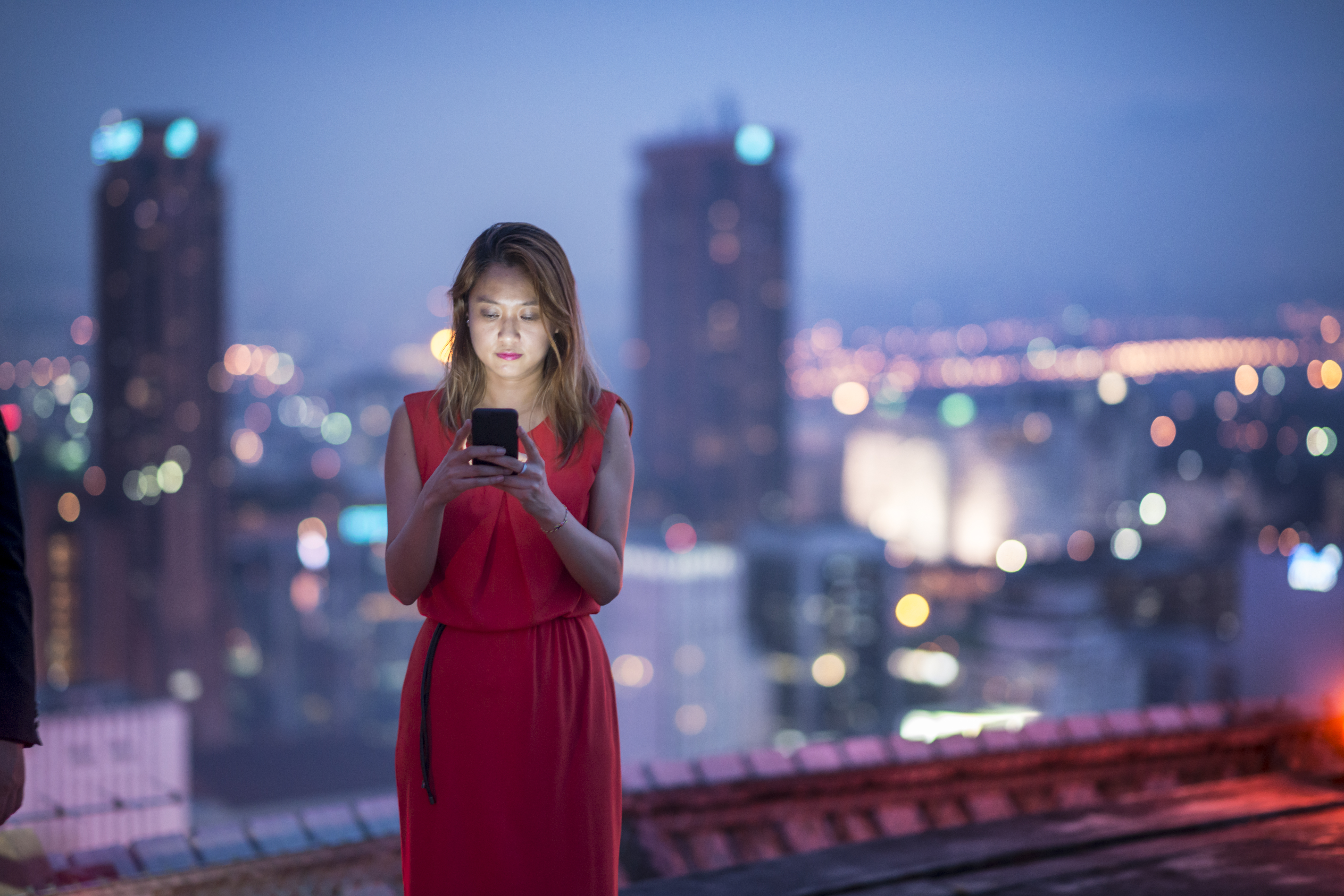 woman-holding-phone-in-usage-30s-cityscape